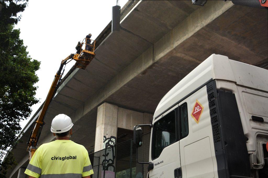 Operarios en la plataforma para colocación de cubiertas laterales en el puente de la AP-9