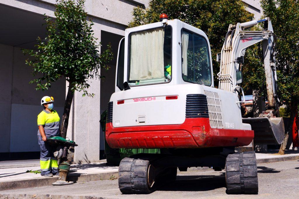Trabajadora de Civis Global junto a una excavadora